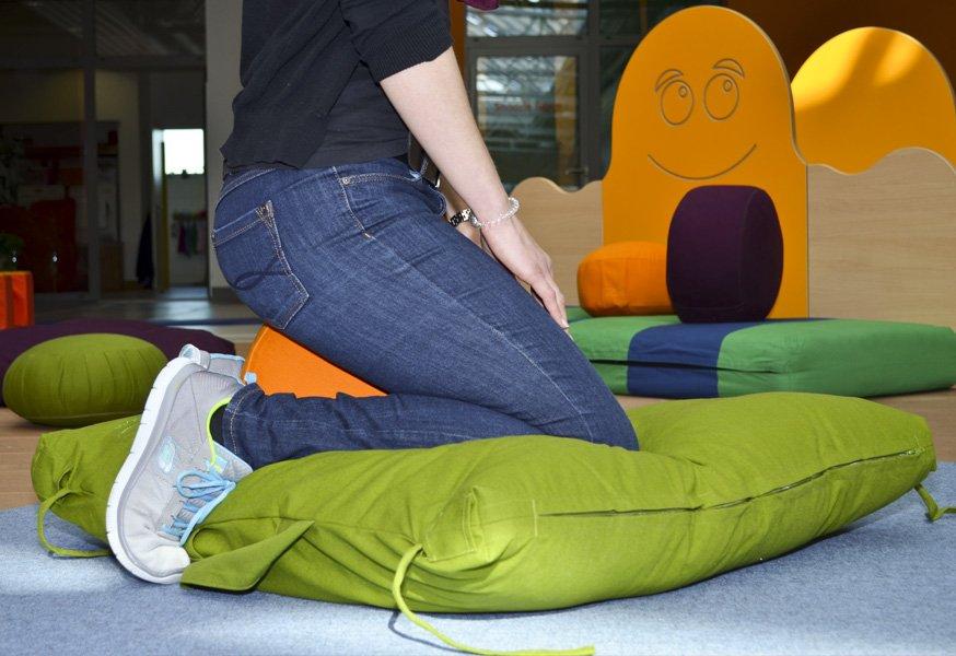 Eine Erzieherin kniet gelenkschonend auf einem Bodenkissen