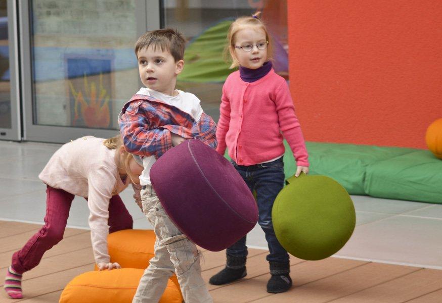 Kinder tragen Bodenkissen an Tragegriffen