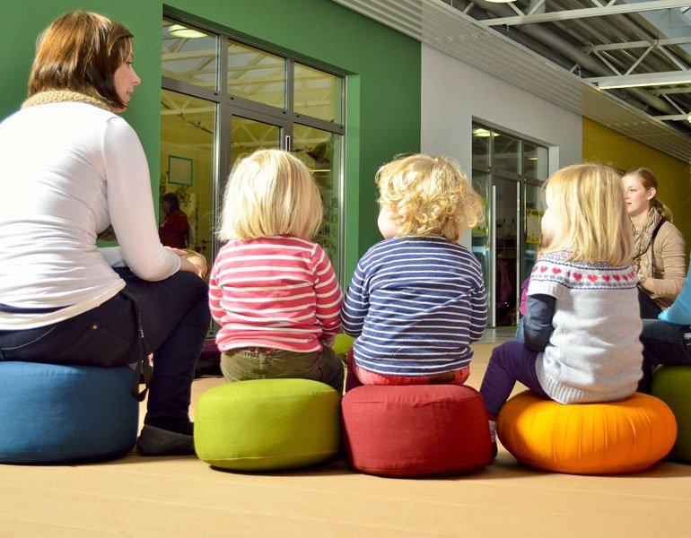 Erzieher und Kinder sitzen auf Bodenkissen im Sitzkreis