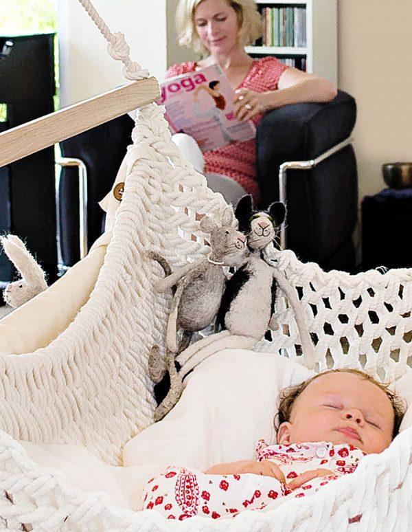 Ein Baby im Babyschwinger während die Mama liest