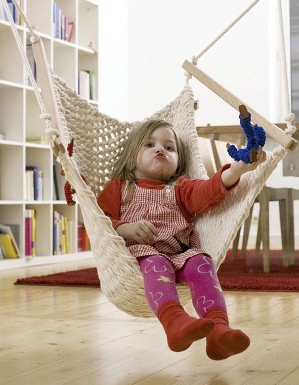 Ein Mädchen spielt im Kinderschwinger