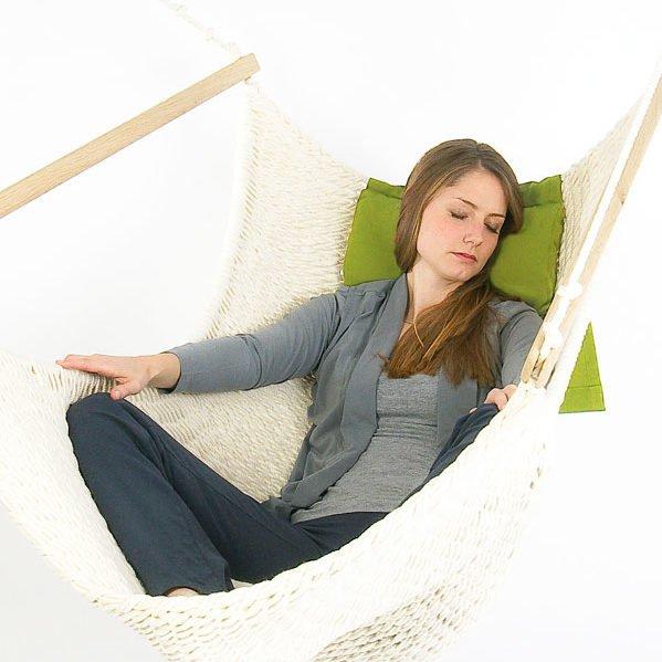 Frau liegt im Traumschwinger auf einem Nackenkissen in grün