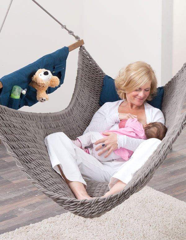 Eine Frau stillt ihr Baby im Traumschwinger