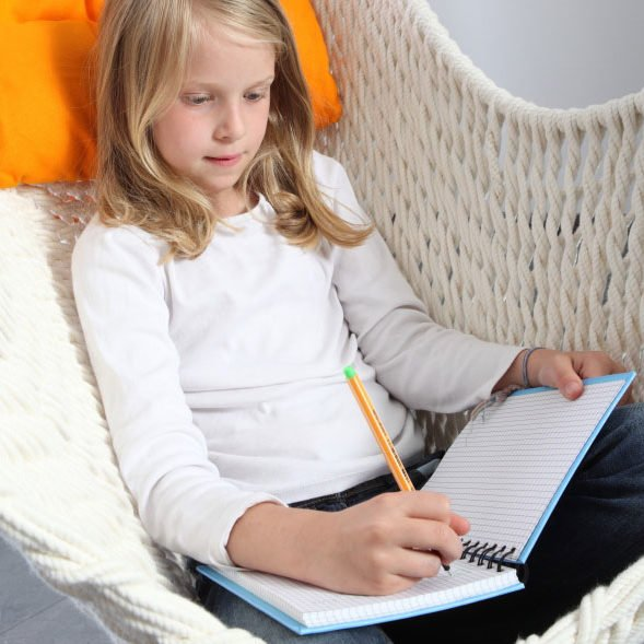 Ein Mädchen schreibt im Hängesessel