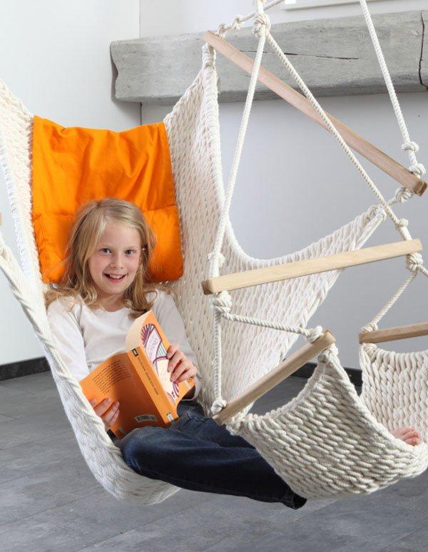Ein Mädchen sitzt in einem Hängessessel mit Fußteil