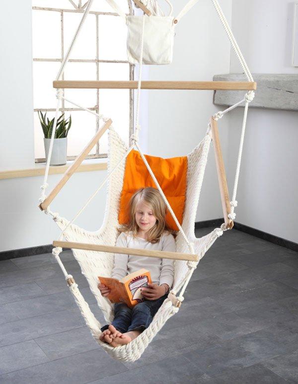 Ein Mädchen liest in einem Traumschwinger L mit Fußteil