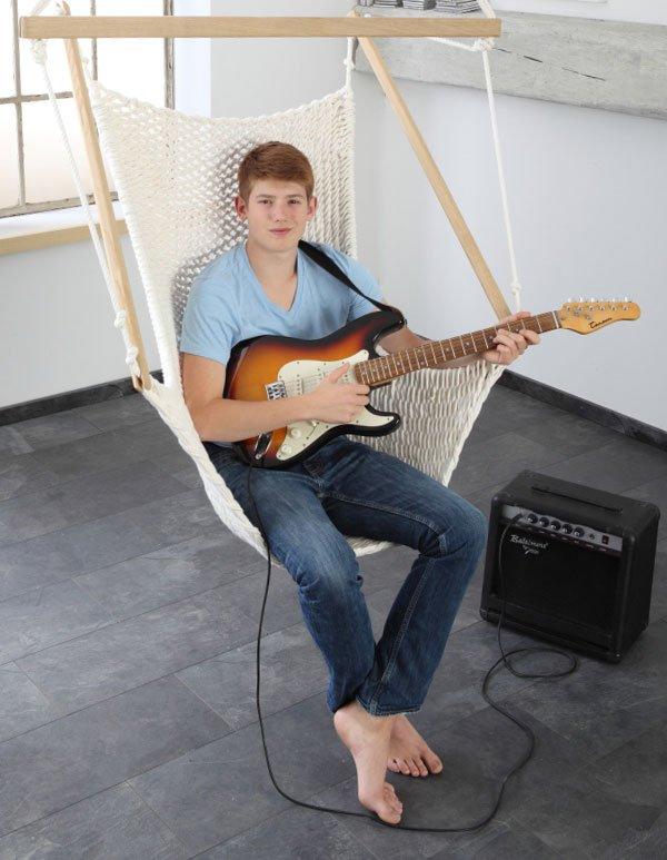 Ein Junge spielt in einem Traumschwinger Gitarre
