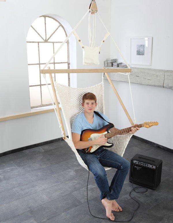 Ein Junge spiel in einem Hängesessel Gitarre