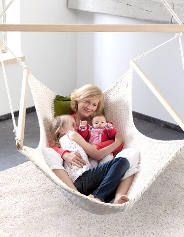 Eine Frau liegt mit ihren Kindern im Familienschwinger