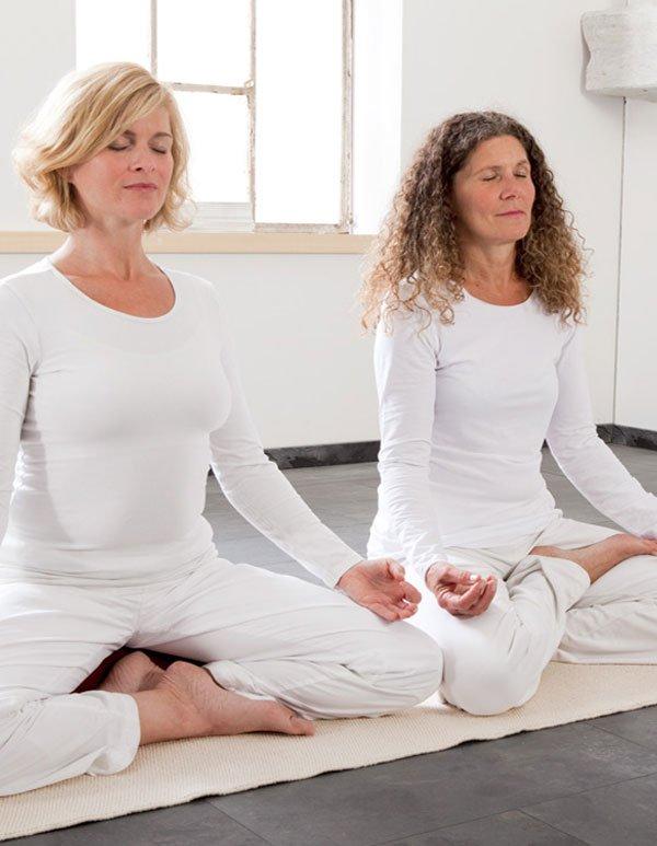 2 Frauen praktizieren Yoga auf einer Yogamatte