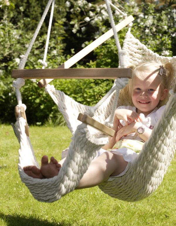Ein Mädchen sitzt in einem Kinderschwinger mit Fußteil