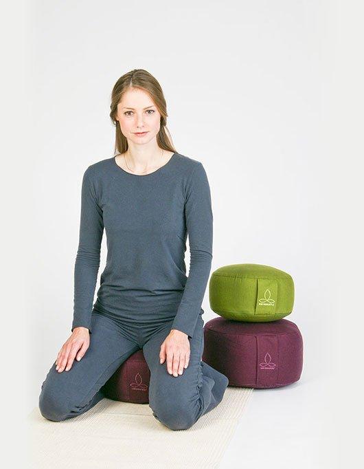 Im Fersensitz auf Yogakissen sitzen