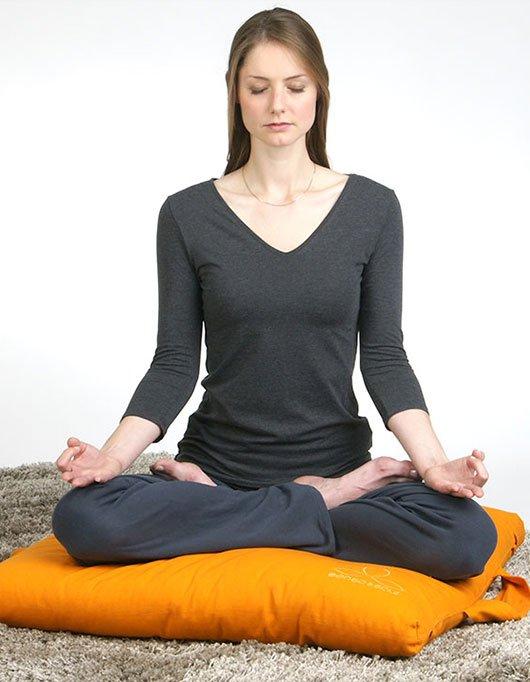 Im Lotussitz auf Yogakissen sitzen