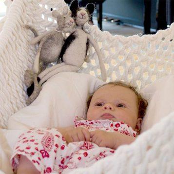 Baby liegt auf der Babymatratze für den Babyschwinger