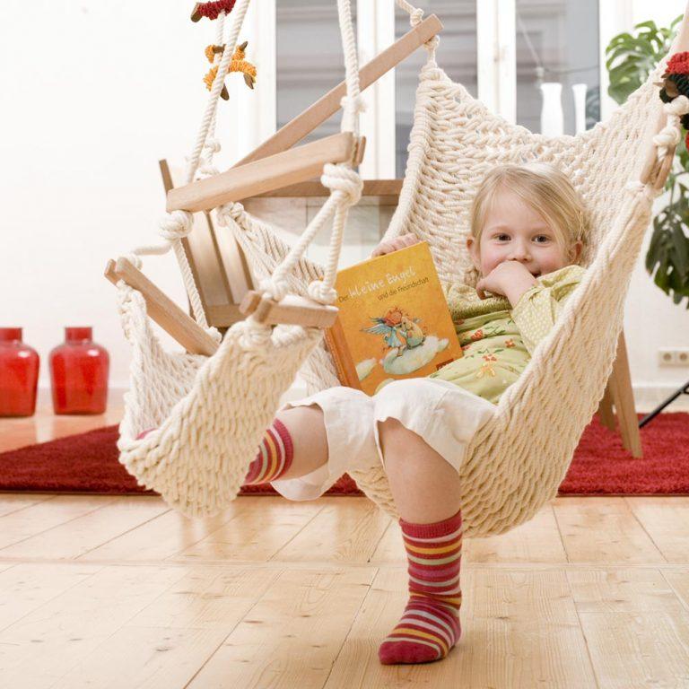 Ein Kind liest im Hängesessel für Kinder
